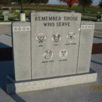 Veterans monument inscribed with the emblem of each branch of the military.