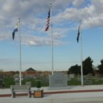 Veterans monument flanked by flags.